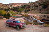 Red pickup camping rig on rocky trail near waterfall in southern Utah