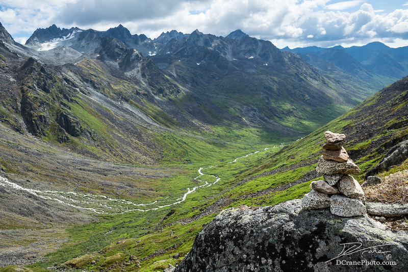 Cairn on rock overlooking massive glacier carved valley in the Talkeetna Mountains, Alaska
