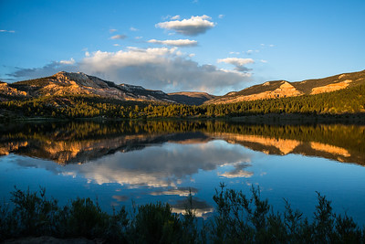 Colorful rock cliffs reflected in calm lake in Southern Utah.