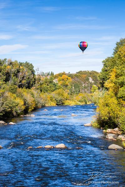 Hot air balloon over river in Colorado
