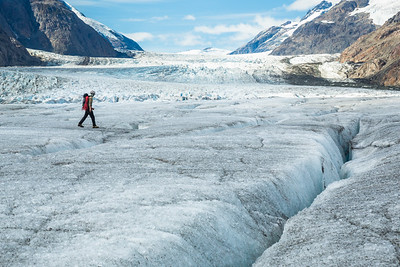 Ice climber walking across the Salmon Glacier near Stewart, British Columbia in remote Canada.