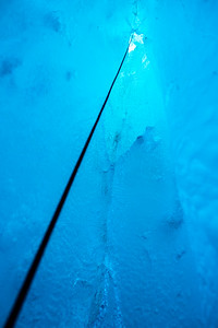 Looking up a climbing rope from deep inside an ice cave in the Salmon Glacier in Canada.