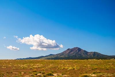 Small peak above arid desert grassland with blue sky overhead.
