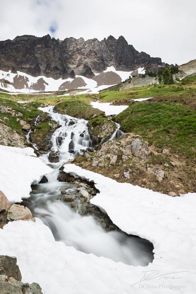 Stream cuts under a snow bridge in high mountain cirque