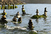 Six Cairns stand against the incoming tide