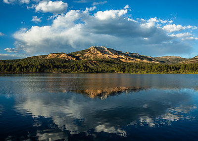 Storm clouds brewing over southern Utah peak reflected in calm lake.