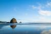 Haystack rock reflected in wet sand of ocean beach