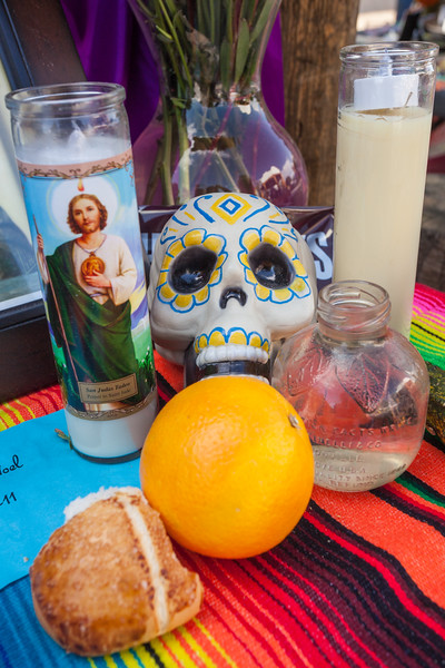 An altar featuring colourful sugar skulls / calaveras, candles, and fruit at the Dia de Los Muertos / Day of the Dead festival in Mesilla, New Mexico, USA