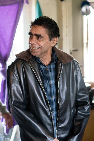 Aboriginal Elder Smiling while Standing Indoors