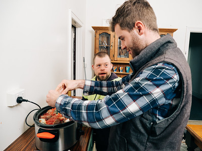 Young Man Looking up at Support Worker while Cooking Together