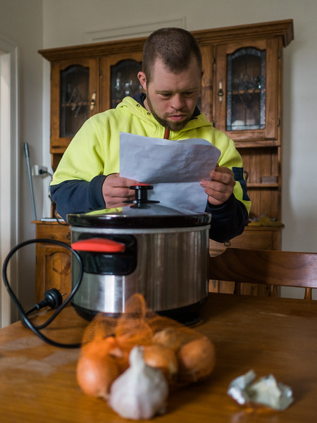 Young Man Reading a Recipe in Preparation for Cooking a Meal