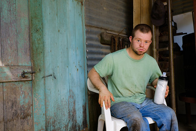 Man with Green T-Shirt seated in Farm Shed