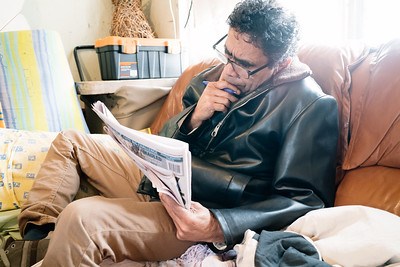Man on a Couch Doing a Newspaper Crossword