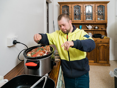 Man Sprinkling Herb on a Meal He Is Cooking