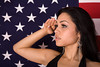Hispanic Woman Saluting in front of an American Flag