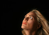 Beautiful Blond Woman Looking Up and Away on Black Background