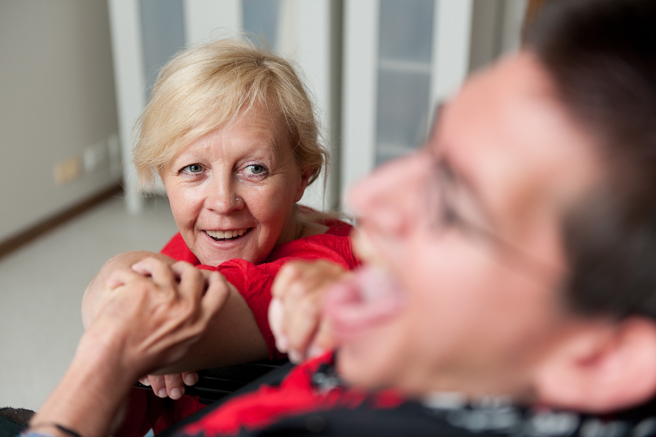 Disability Support Worker looking at a Man, smiling