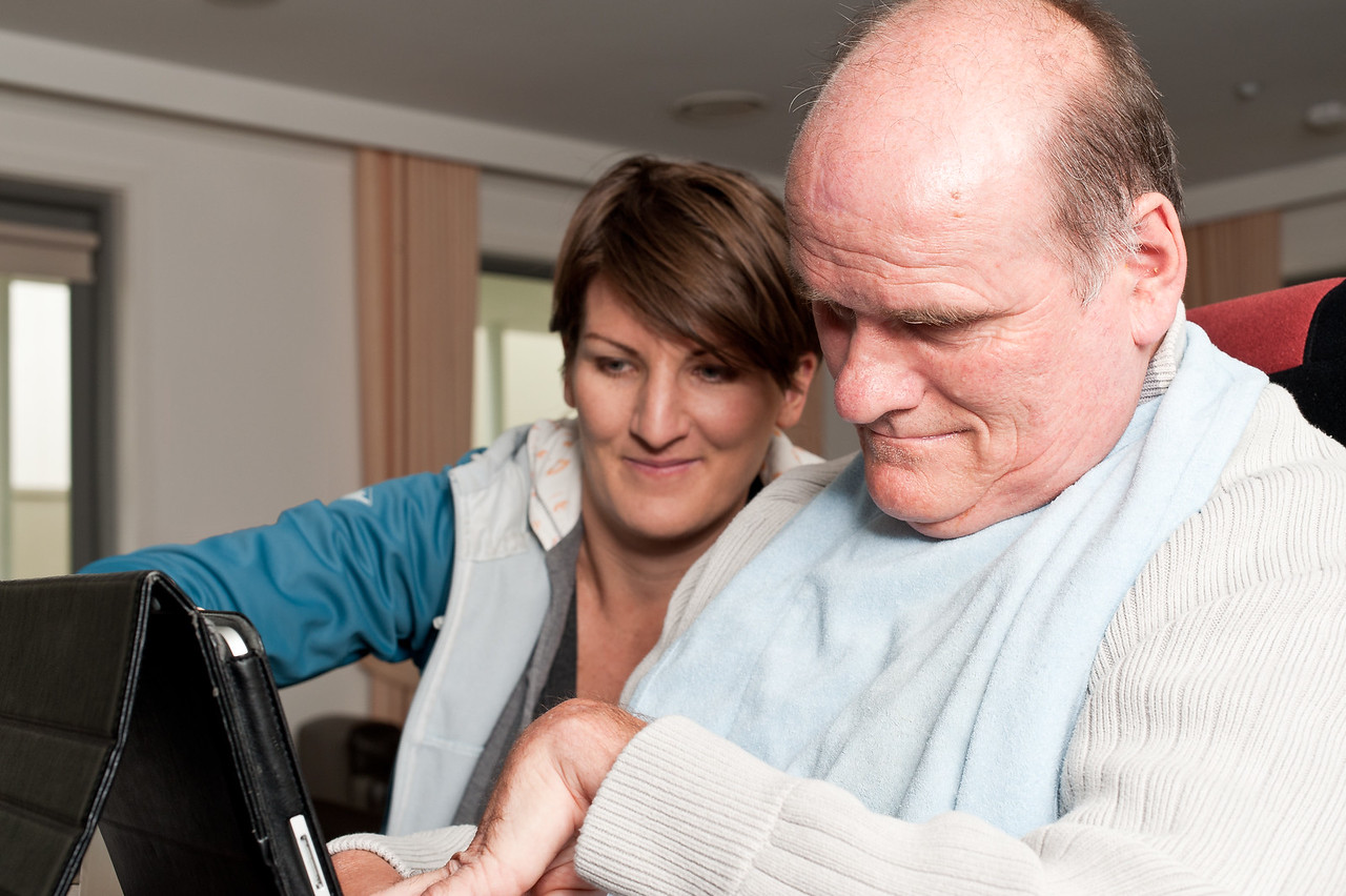 Woman assisting man with disability to use computer inside his home.
