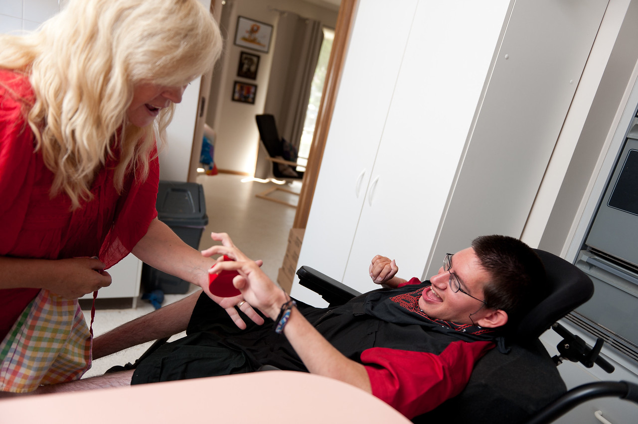 """Woman helping a young man to put away dishes.  This photo can be used to illustrate the importance of promoting engagement in meaningful activity.  This whole concept and practice has been referred to as Person-Centred Active Support and has extensive empirical evidence to support its importance in promoting a great quality of life for all people with a disability, """"irrespective of degree of disability or the presence of extra problems*  * Mansell, J., Beadle-Brown, J., Ashman, B., & Ockenden, J. (2004). Person-Centred Active Support. Pavilion Publishing (Brighton) Ltd.."""