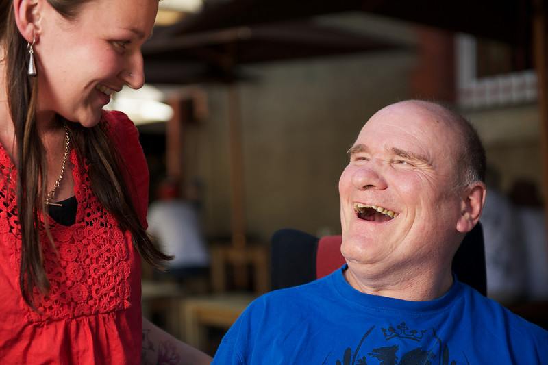 Man with a disability laughing with a woman at a cafe
