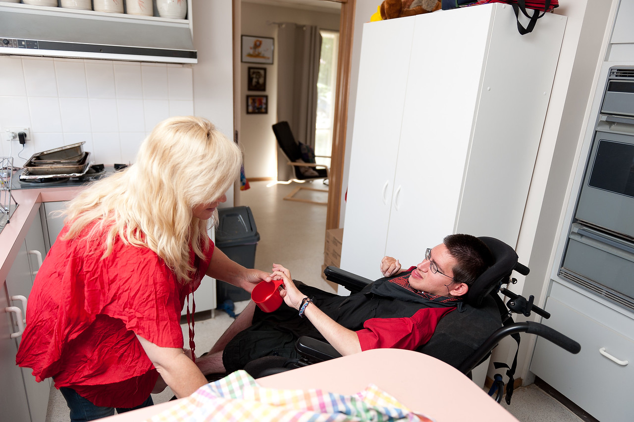 """Woman helping a young man to dry dishes.  This photo can be used to illustrate the importance of promoting engagement in meaningful activity.  This whole concept and practice has been referred to as Person-Centred Active Support and has extensive empirical evidence to support its importance in promoting a great quality of life for all people with a disability, """"irrespective of degree of disability or the presence of extra problems*  * Mansell, J., Beadle-Brown, J., Ashman, B., & Ockenden, J. (2004). Person-Centred Active Support. Pavilion Publishing (Brighton) Ltd.."""