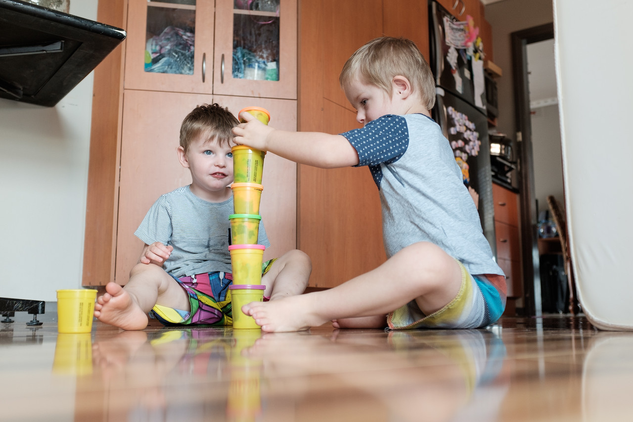 Boy Stacking Toys while Another Watches On