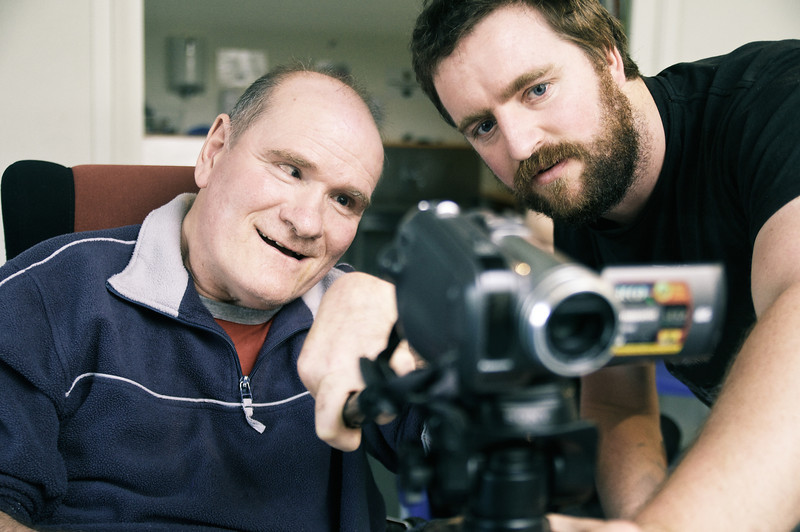 Man with a Disability using a Video Camera with help of a Support Worker