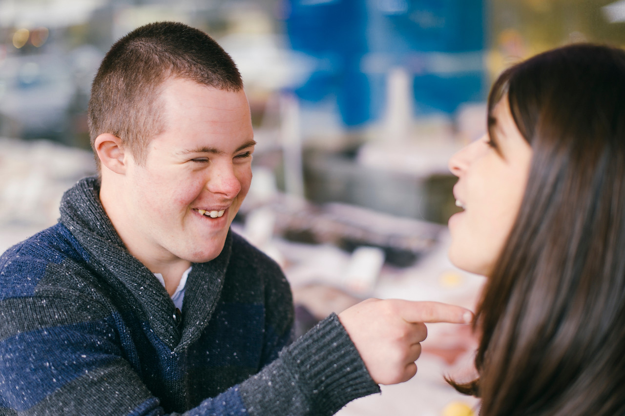 Seventeen-Year-Old boy with Down Syndrome laughing with a Young Woman of Twenty.
