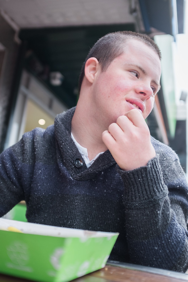 Teenager with Short Hair eating at a Stree Cafe