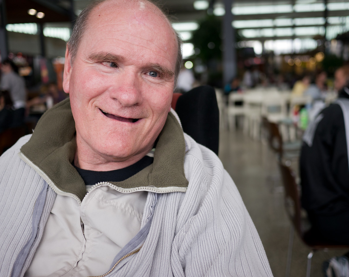 Mature man with a disability at shopping centre, with a blurred background