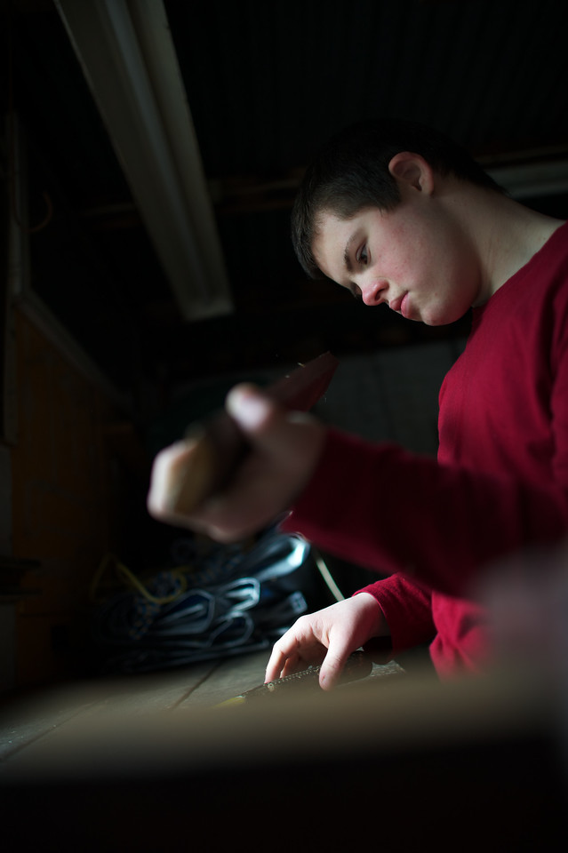 Teenage boy doing woodwork, inspecting a piece of wood he is working on