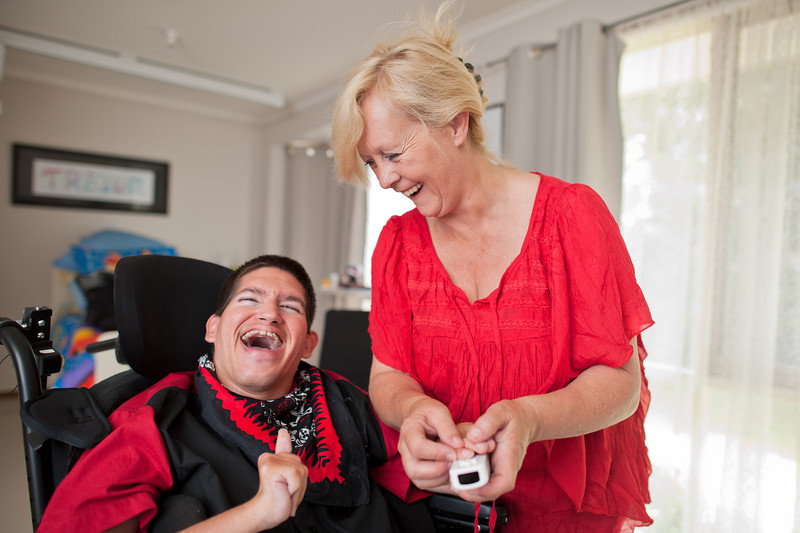 """Young Man being assisted to use a Video Game Controller by his Support Worker.  This photo can be used to illustrate the importance of promoting engagement in meaningful activity.  This whole concept and practice has been referred to as Person-Centred Active Support and has extensive empirical evidence to support its importance in promoting a great quality of life for all people with a disability, """"irrespective of degree of disability or the presence of extra problems*  * Mansell, J., Beadle-Brown, J., Ashman, B., & Ockenden, J. (2004). Person-Centred Active Support. Pavilion Publishing (Brighton) Ltd.."""