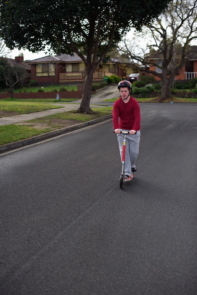Teenager Riding a Scooter down a Suburban Road