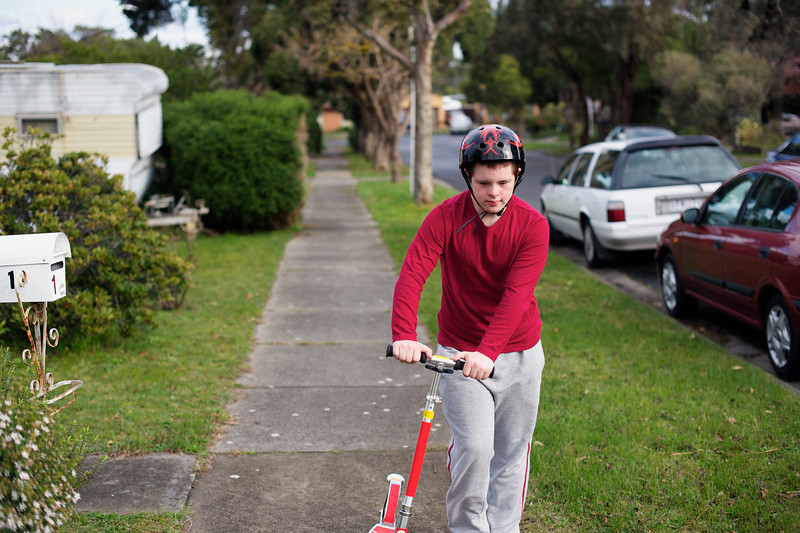Teenage boy pushing a scooter up a footpath
