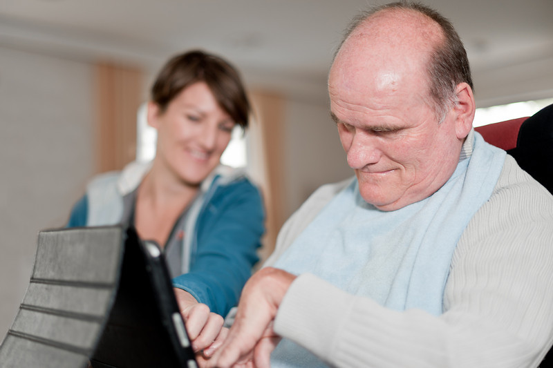 Woman assisting mature aged man with disability to use computer in his home.  She is blurred in the background.