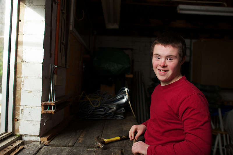 Teenager in a Garage with a Hammer