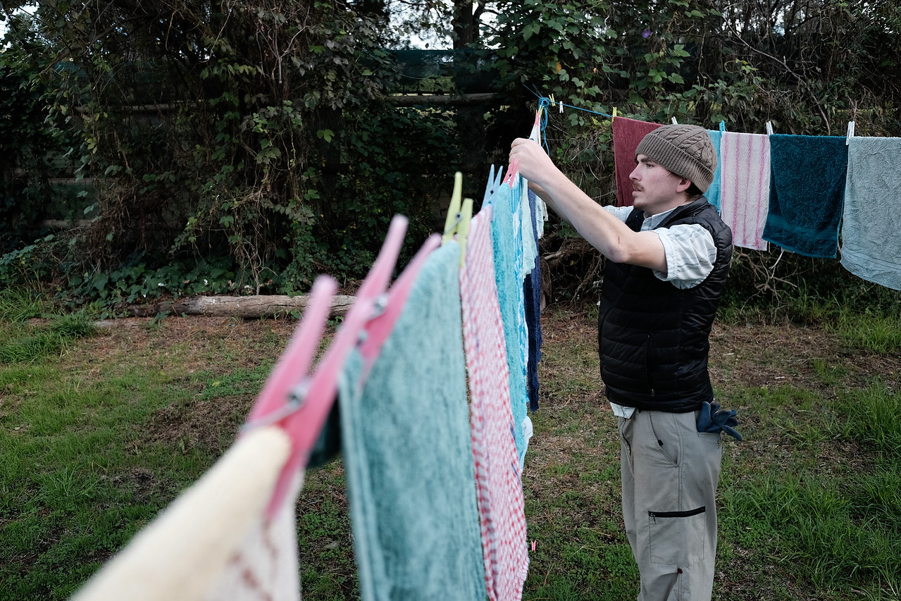 Man Hanging out Towels to Dry on Clothesline