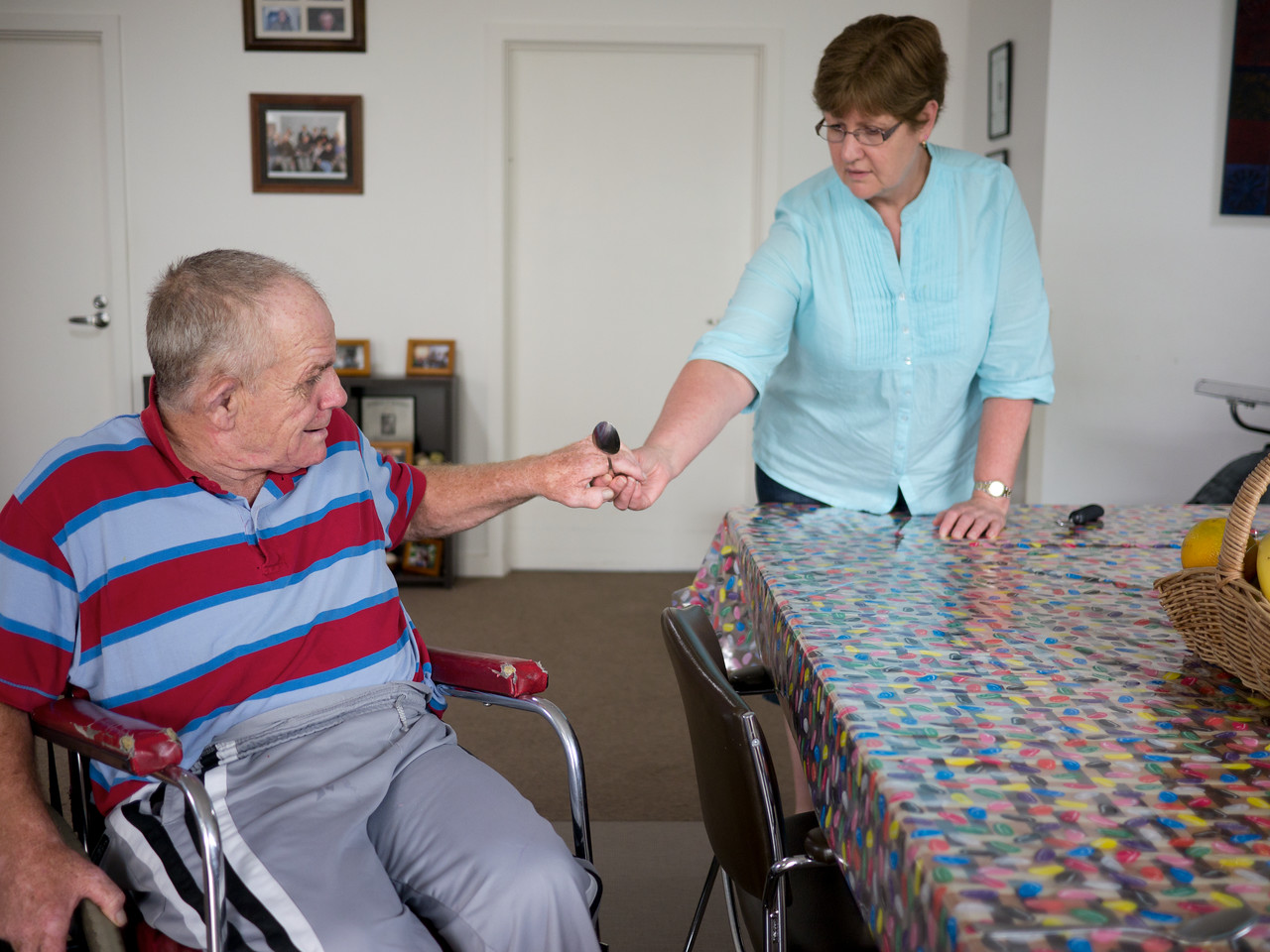A home carer is handing a spoon to a senior man with a disability as he sets a table in his home.