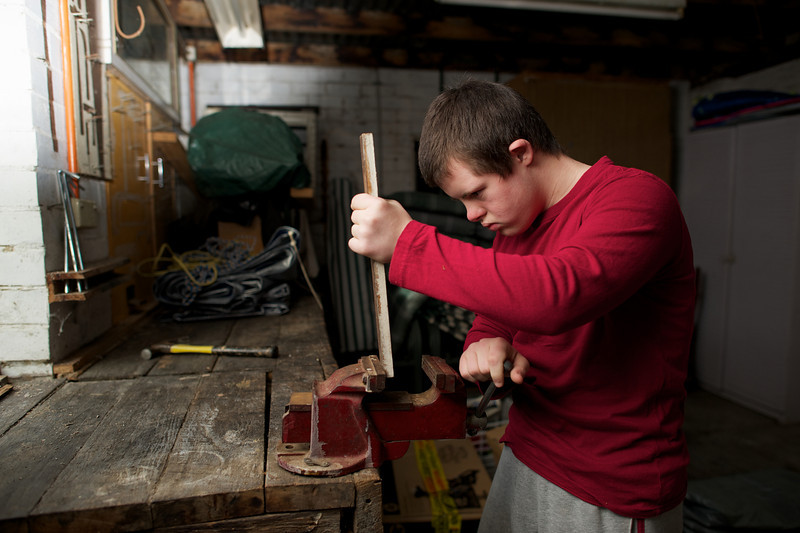 Teenager placing wood in a vice