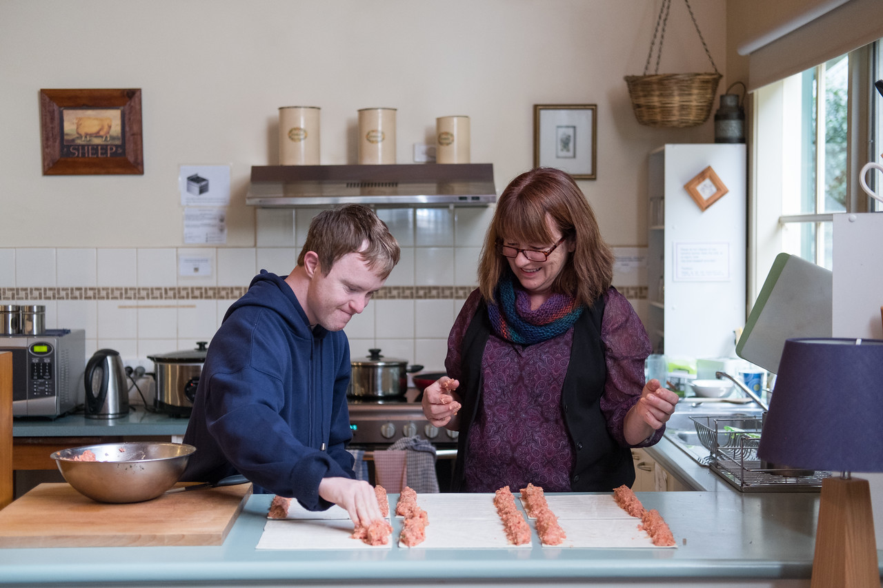Young Man Making Sausage Rolls with Help from Support Worker