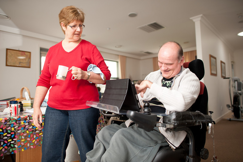 Man in his fifties operating a table computer while in his wheelchair with a female support worker walking past.