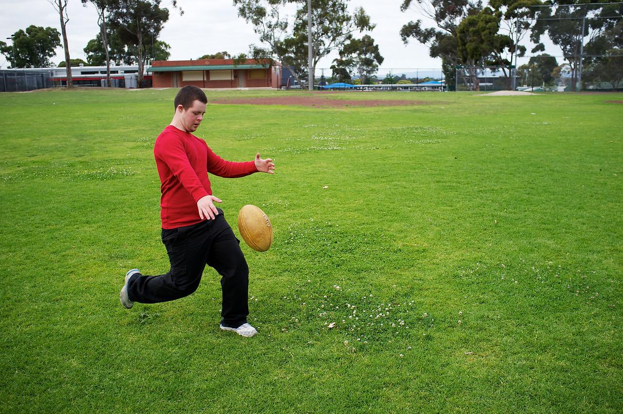 Sixteen-year-old boy kicking football at a suburban park