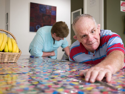 """This man, 66 years of age, is setting a table.  He has a disability and is photographed in his home.  This photo can be used to illustrate the importance of promoting engagement in meaningful activity.  This whole concept and practice has been referred to as Person-Centred Active Support and has extensive empirical evidence to support its importance in promoting a great quality of life for all people with a disability, """"irrespective of degree of disability or the presence of extra problems*  * Mansell, J., Beadle-Brown, J., Ashman, B., & Ockenden, J. (2004). Person-Centred Active Support. Pavilion Publishing (Brighton) Ltd.."""