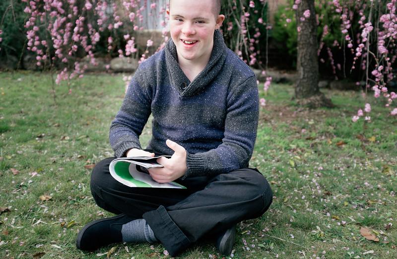 Teenage boy sitting on a lawn cross legged with a magazine.