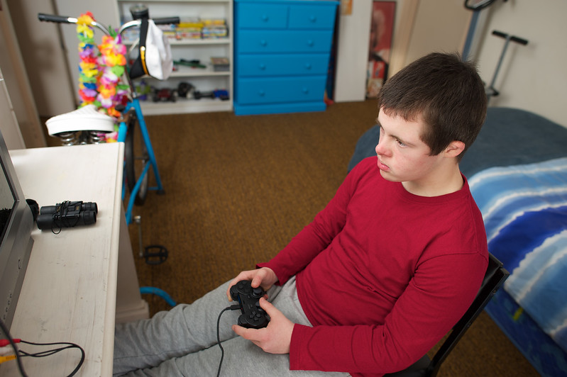 Teenager in his bedroom playing a video game