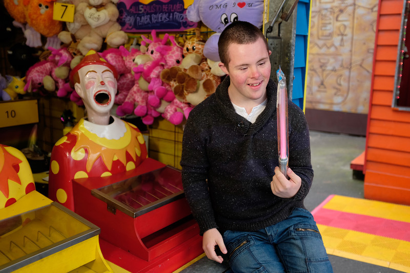 Teenage Boy with Down Syndrome holding prize at Fun Fair