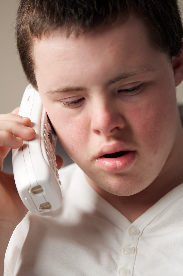 Sixteen-year-old boy talking on telephone