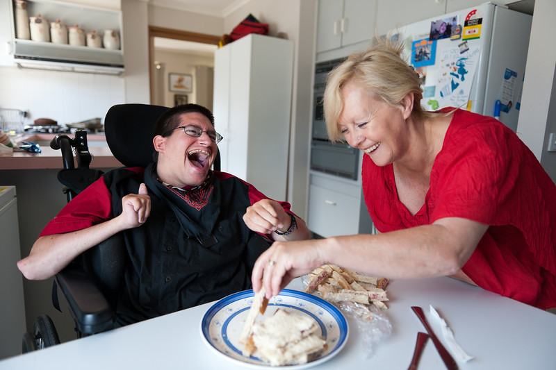 Man being assisted to remove crusts from a sandwich plate that he has prepared for his lunch.