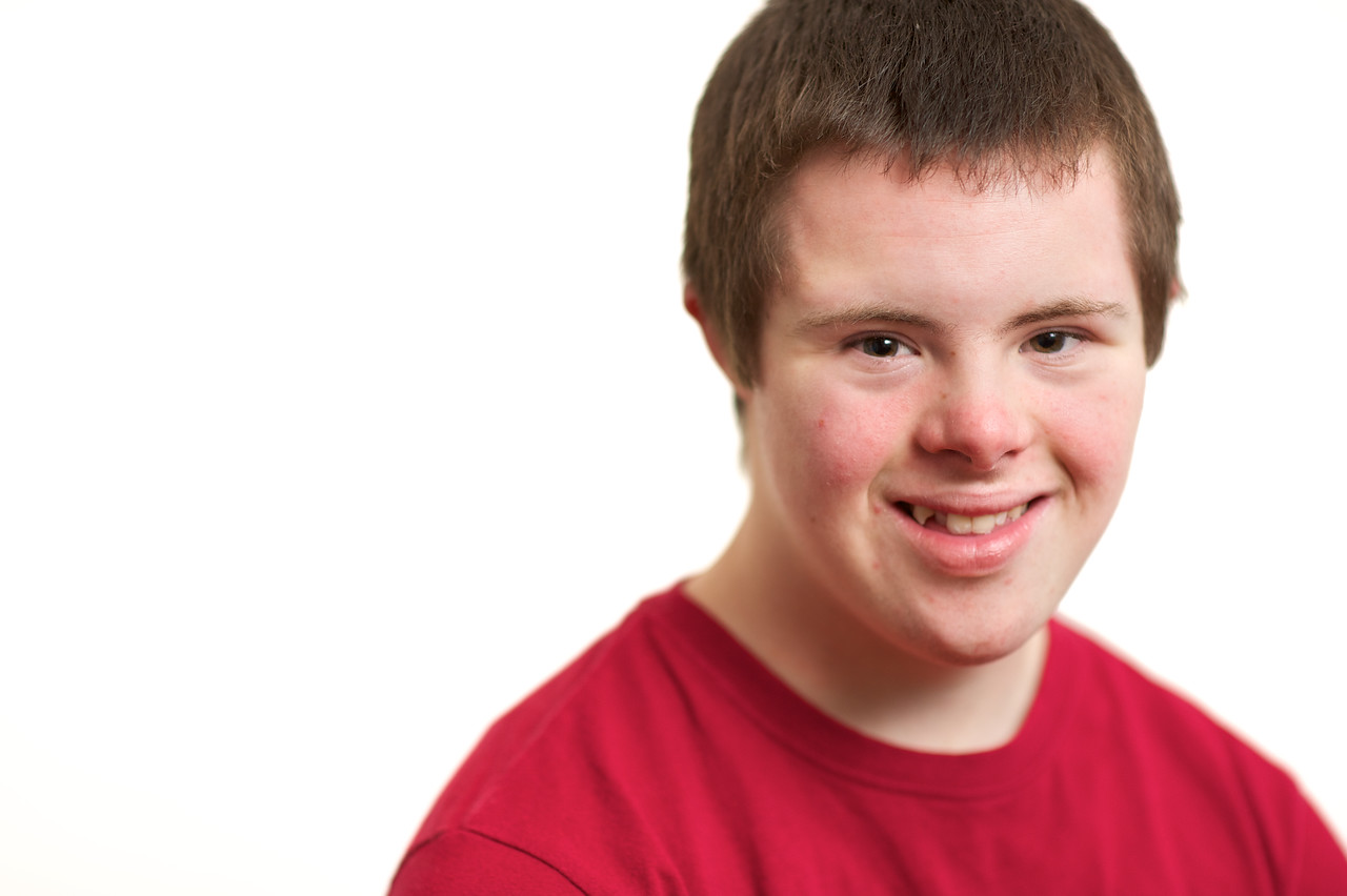 Fifteen-year-old boy smiling, photographed on a white background