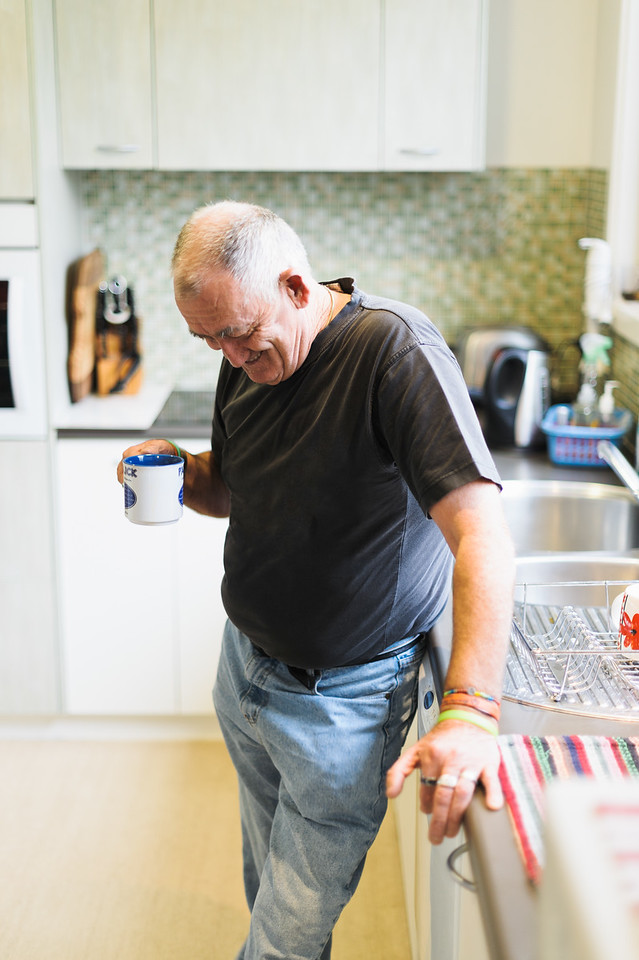 Smiling man in his 60s enjoying a cup of tea in his kitchen.